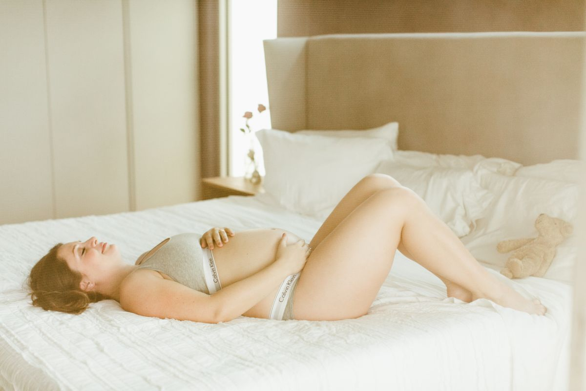 pregnant mom laying on bed