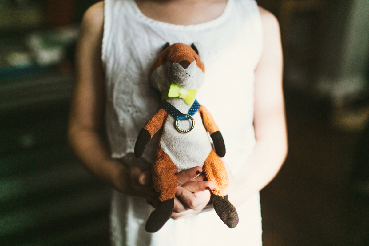 stuffed animal holding wedding rings