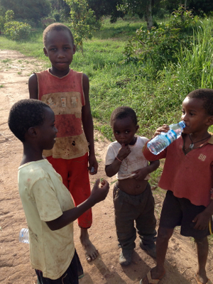 Sharing a clean bottle of water with our younger friends in Bweya, where a bore hole/ well is desperately needed