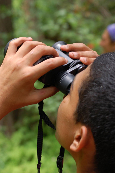 Boy with binoculars at El Ranchito Nature Discovery Camp, Austin