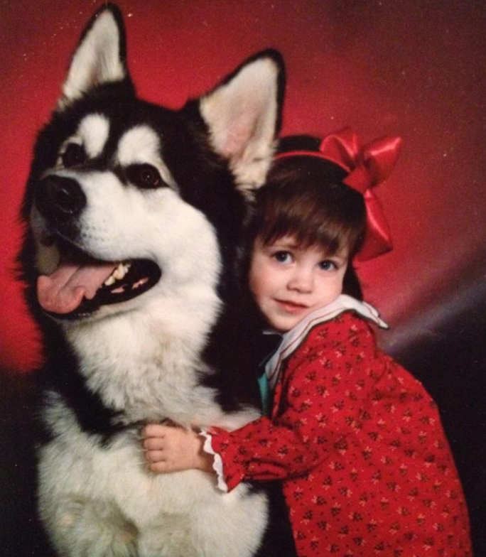An image of Lindsey Ascheman when she was younger hugging a Husky