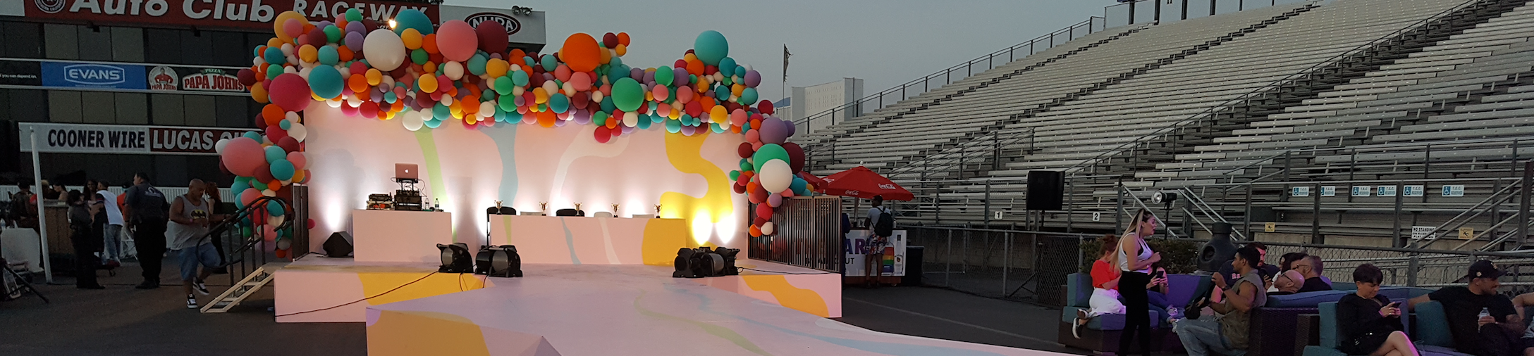 An outdoor stage design from an LGBTQ+ event with colorful balloons and splatter paint