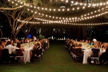 An image of outdoor wedding reception with string lighting hanging above