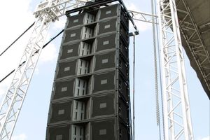 An image of a large JBL speaker rigged to a truss at an outdoor event