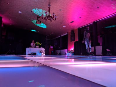 An image of a party with a lit-up dance floor and pink lighting