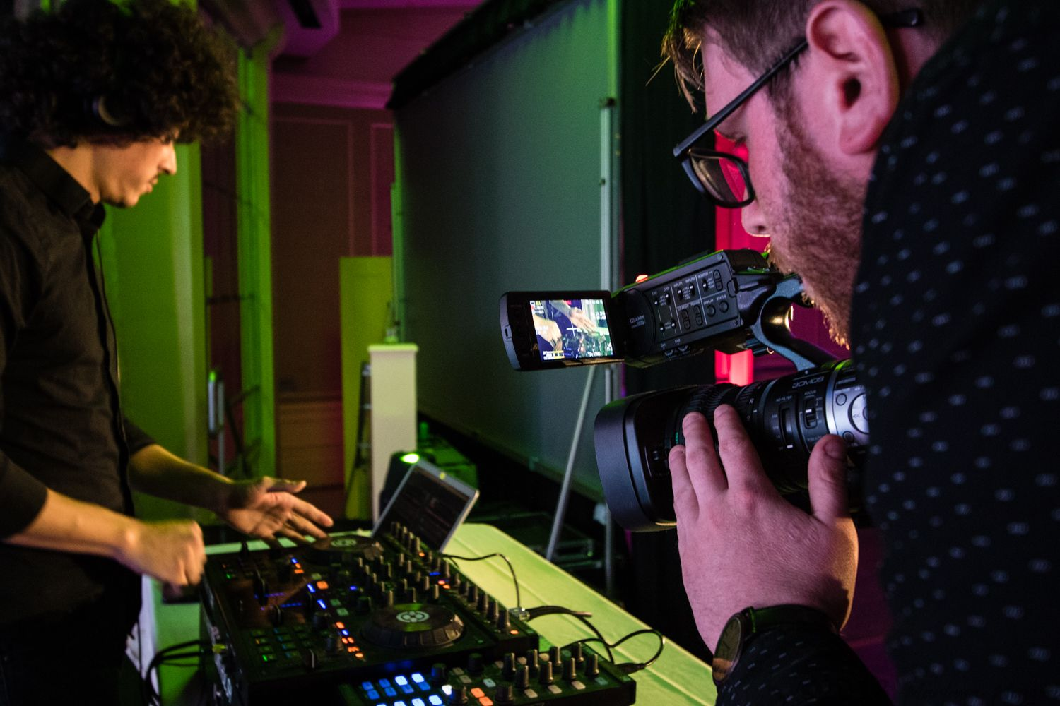 A videographer getting a close-up of a DJ at a nonprofit gala