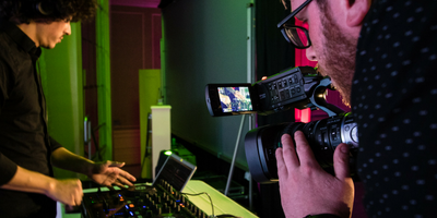 A videographer getting a close-up of DJ equipment at a gala