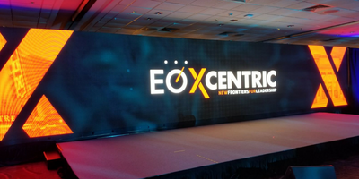 A large LED video wall displaying EO XCentric's logo