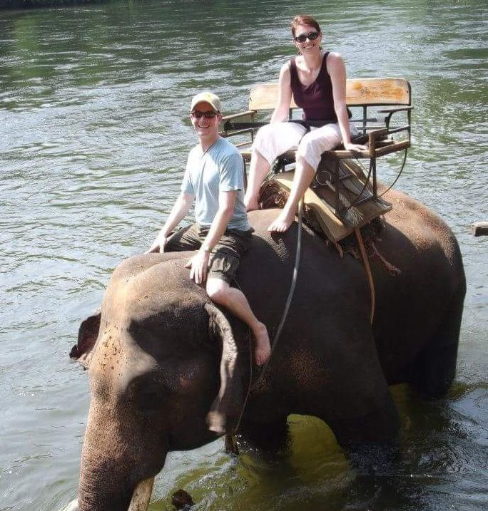 An image of Michael Greig riding an elephant with Amanda Greig