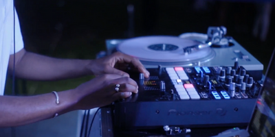 A DJ spinning at a party on Pioneer equipment