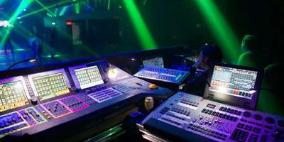 Lighting designers sitting at the lighting control center at an event