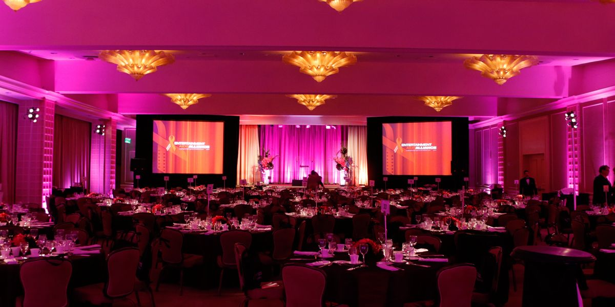 A large gala set up in a hotel ballroom with pink lighting and a two screen display