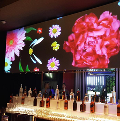 An image of a projection above a bar at a corporate holiday party
