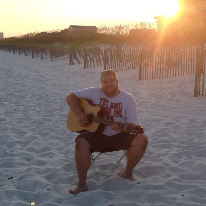 An image of Rob Burgess playing the guitar on a beach