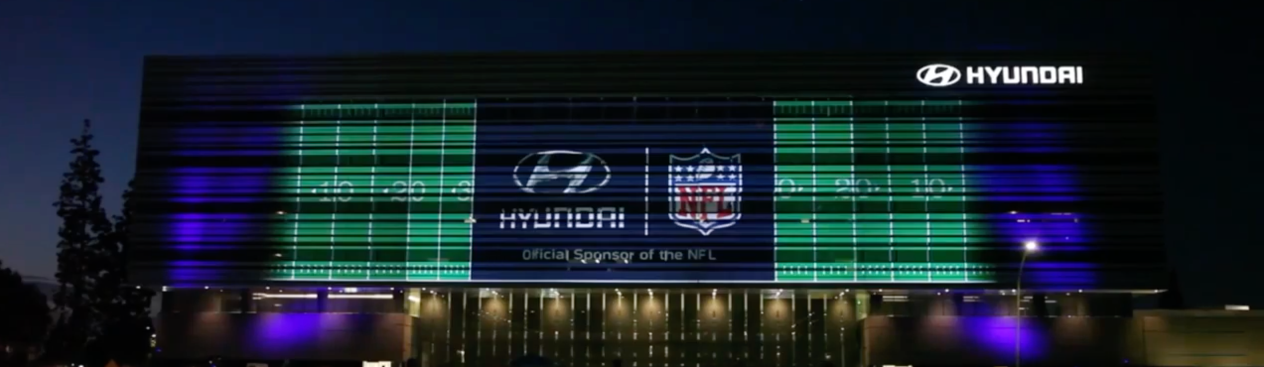 A large NFL video projection display on the side of the Hyundai headquarters