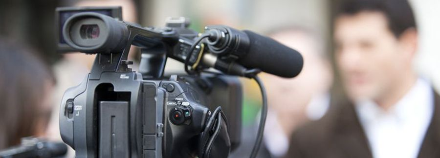 Video camera taping Hispanic reporter