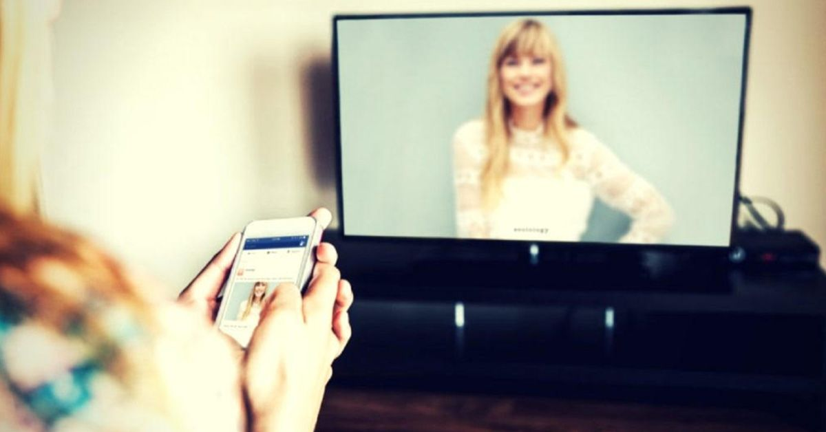 Woman on her phone with TV in background