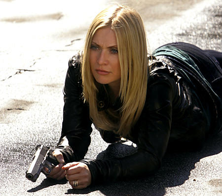 emily procter csi set still gun laying.jpg