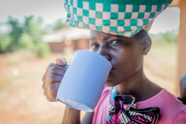Sauit Kuu- girl drinking cup of water, with water jub on head, and baby on back close up- February 2019 (1).jpg
