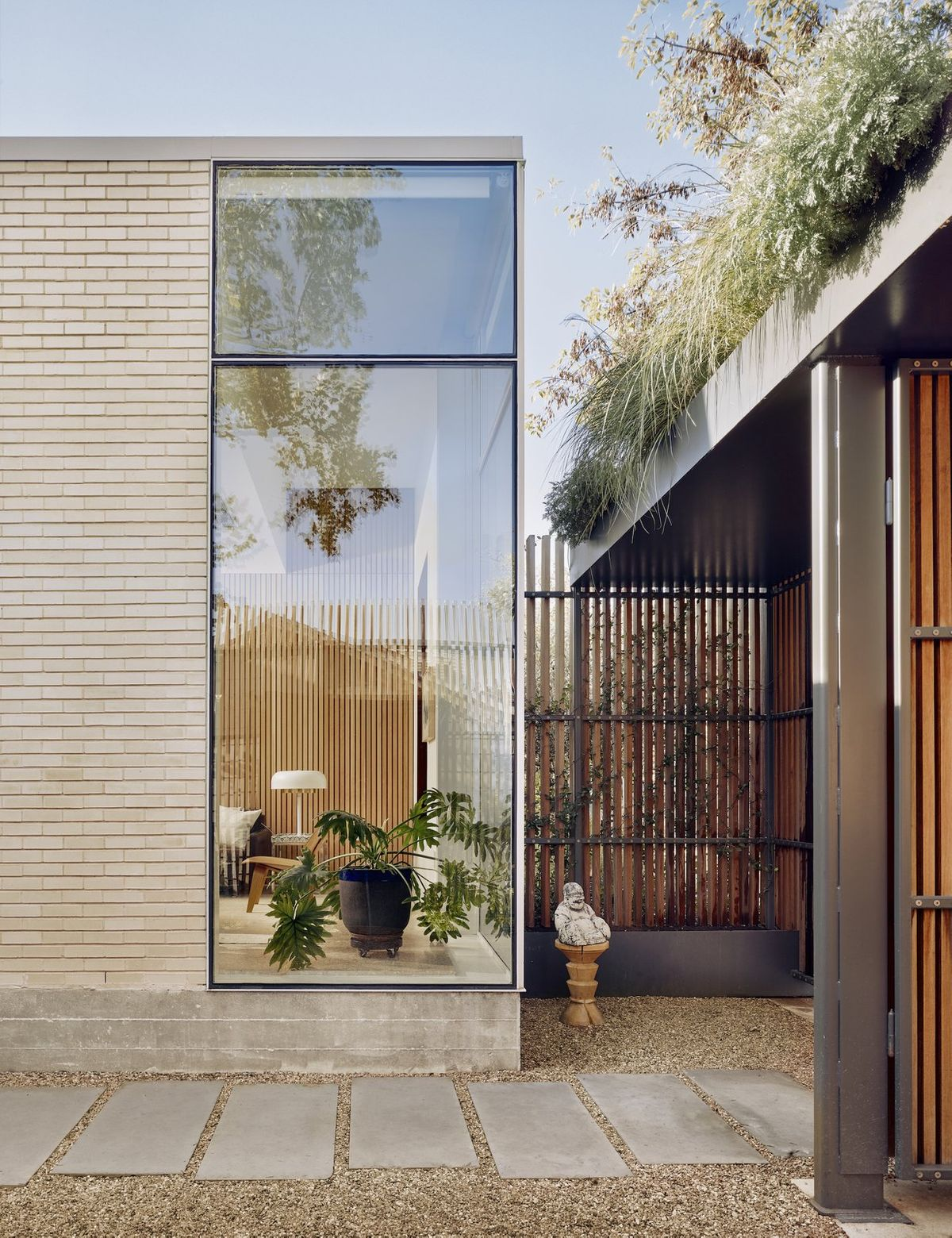 the-entrance-is-through-an-enclosed-courtyard-which-features-ipe-brazilian-walnut-timber-fencing-with-an-exposed-painted-steel-structure-topped-with-planters-the-living-room-is-visible-through-a-glazed-corner.jpg