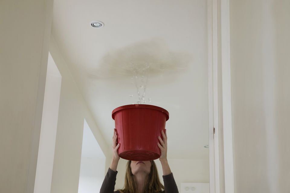 woman-holding-out-a-bucket-to-stop-a-roof-leak-106958449-5910d02c5f9b5864703afaa8.jpg