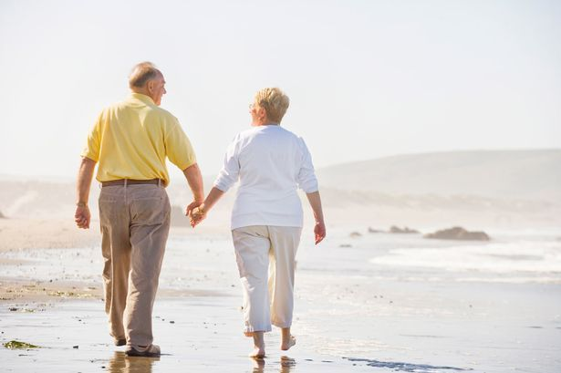 Mature-couple-walking-on-beach.jpg