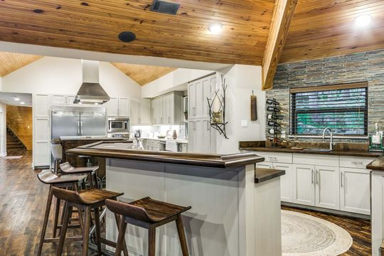 Custom Gourmet Kitchen with Wood Ceiling and Stone Veneer
