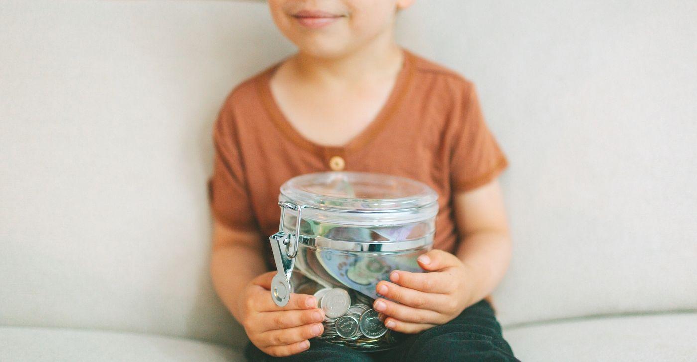 a-child-holding-a-jar-of-money-HJGZVKM.jpg