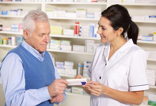 Pharmacist serving senior man in Pharmacy