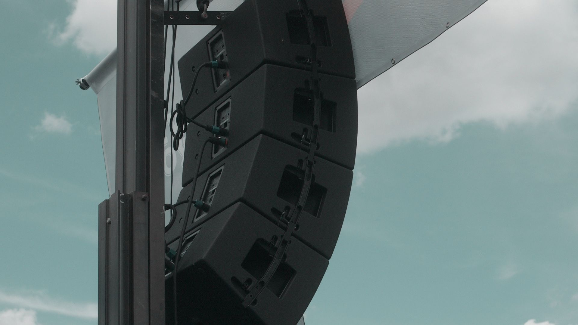 Hanging speaker on a stage at an outdoor event
