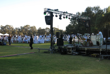 Image of stage at an outdoor event with audience all dressed in white