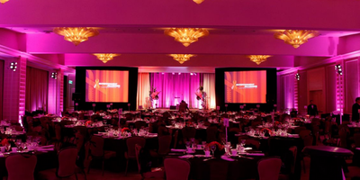 Large gala with two screens and pink lighting