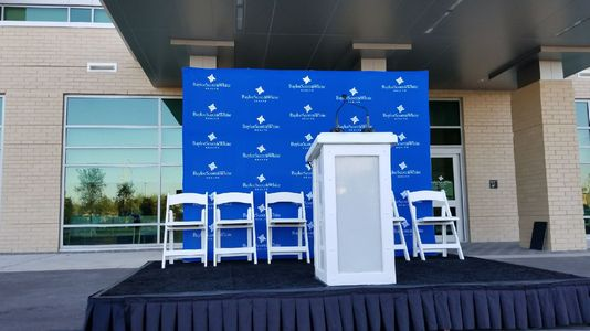 Small stage with blue branded back drop and white podium