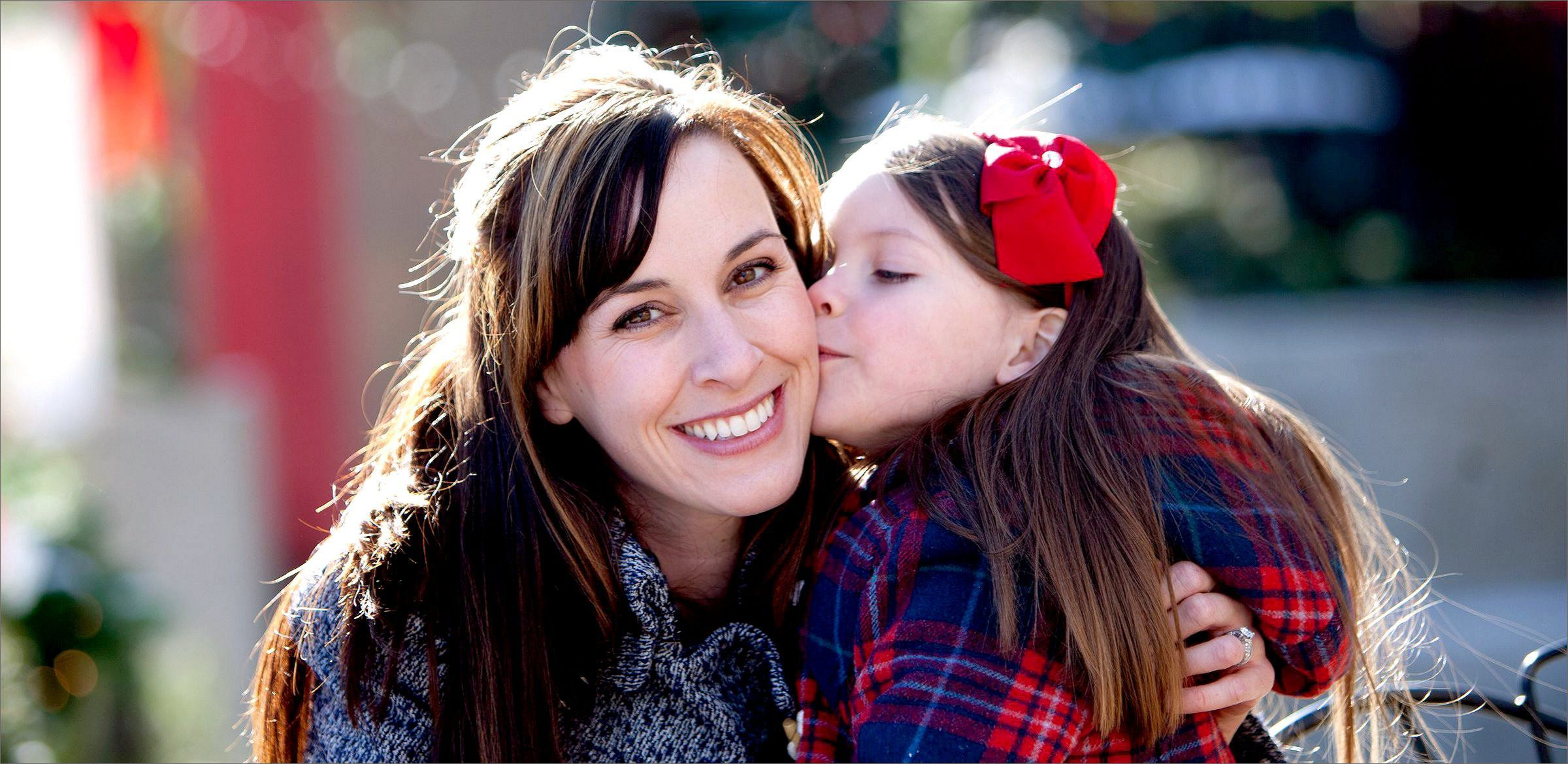 Daughter kissing her mom on the cheek  during a photo shoot at Little Man Ice Cream's Tree Farm