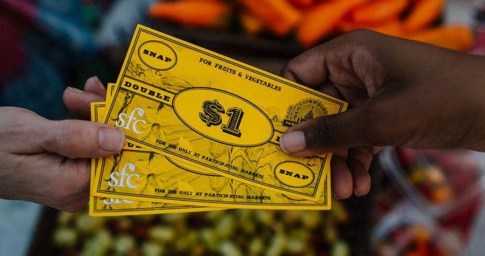 Hands Passing Yellow Market Dollars