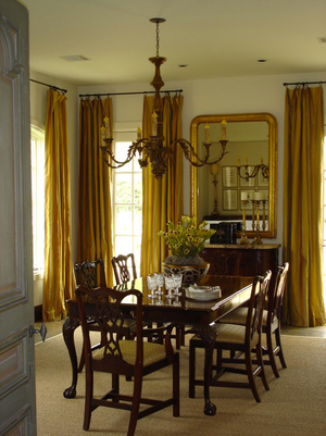Traditional dining room with ochre draperies and dark wood