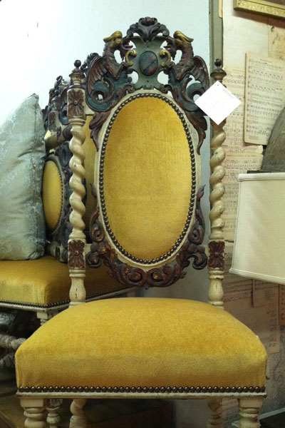 Ochre/mustard/yellow upholstered chair with decorative scrolling