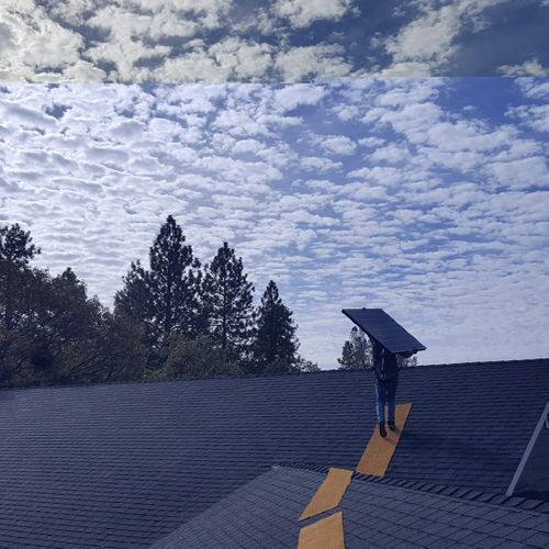man installing solar panels on a home