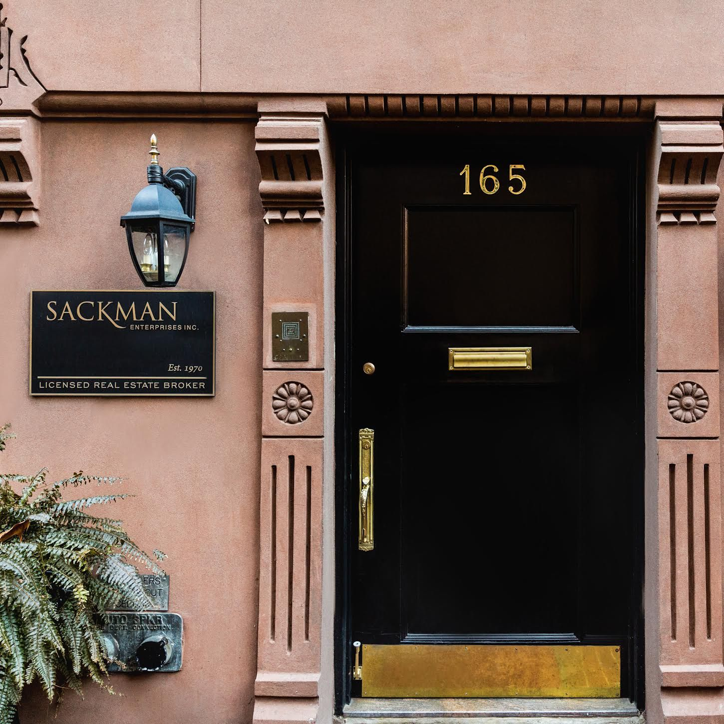 Image of the Sackman Enterprises building's front door on a light pink wall with black and gold trim