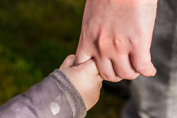 child holding parent's hand.jpeg