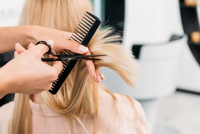 cropped-image-of-hairdresser-trimming-ends-of-blon-SZ5Z8W8.jpg