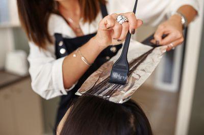 hairdresser-works-with-customer-hair-closeup-VHYDAY4.jpg