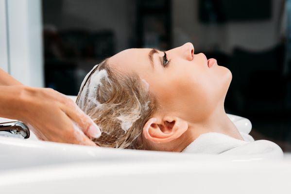 side-view-of-hairdresser-washing-hair-for-customer-PJXVZWE.jpg