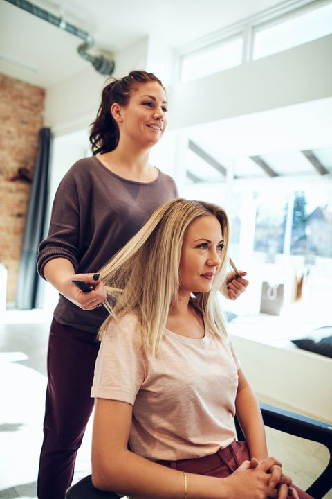 smiling-young-woman-getting-her-hair-done-at-a-sal-7YX8ZFS.jpg
