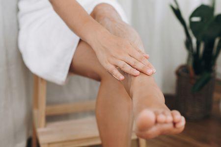 young-woman-applying-cream-on-her-legs-after-shavi-9MA5XYZ.JPG