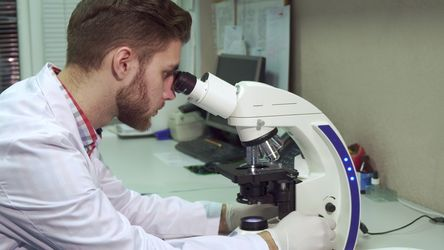 Man looking through the microscope at the laboratory