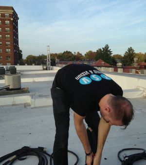 Joel Dodson running cable on a rooftop for CWE Halloween
