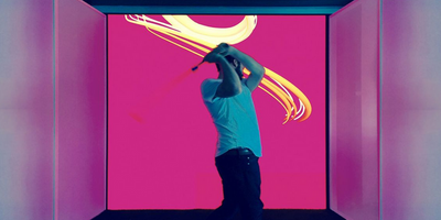 A man swinging a golf club in front of a video display