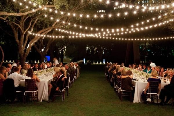 Guests seated under string lights at an outdoor wedding reception