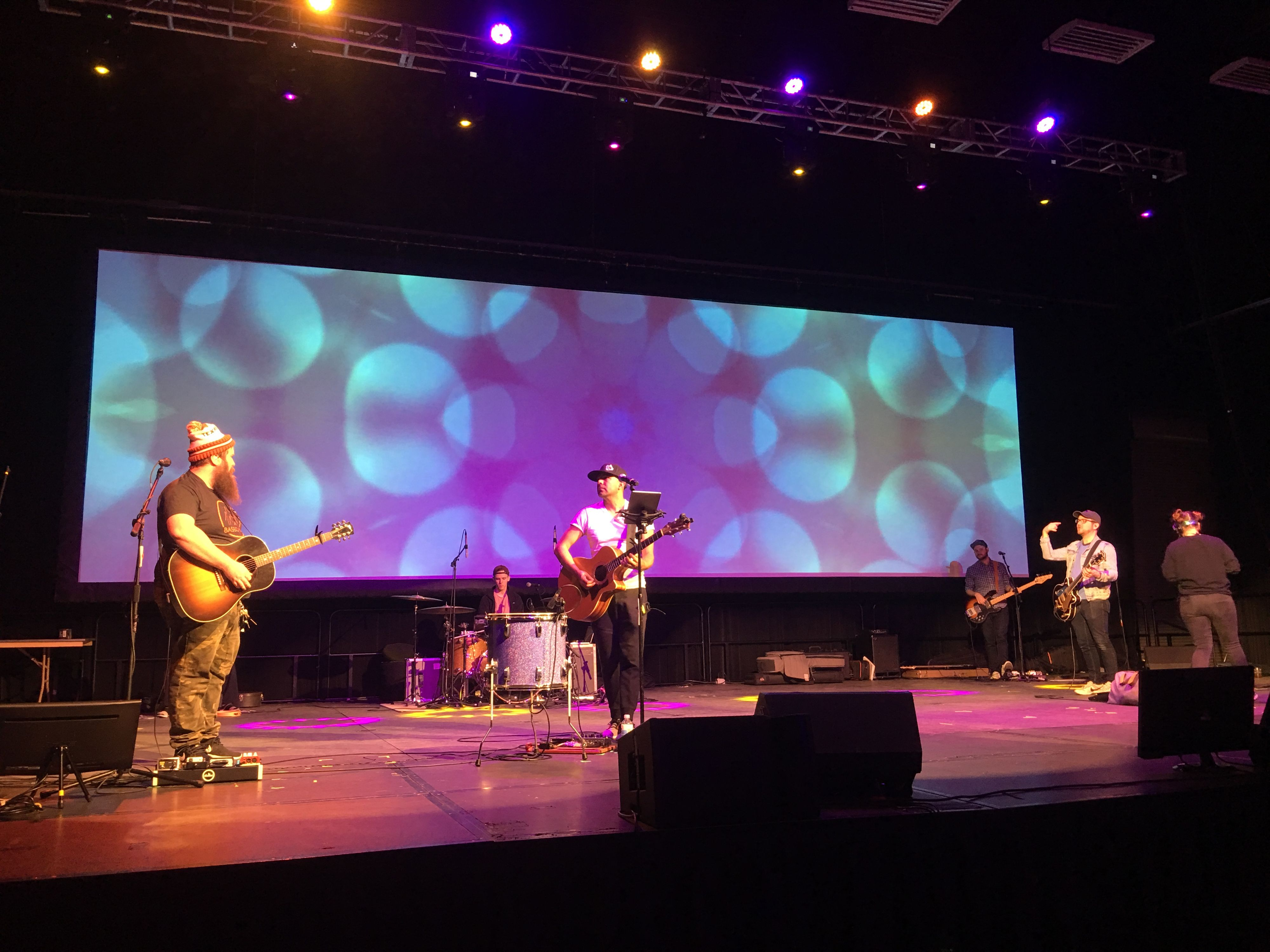 A band playing on stage in front of a large projection display at a St. Louis Conference